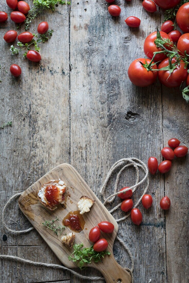 Tomatoes and snack of toast with cheese and tomato jam on a vintage wooden table