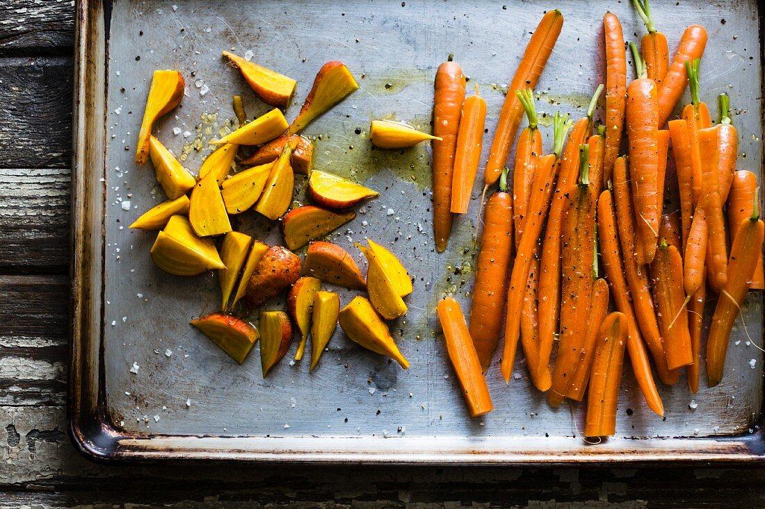 Rohe Karotten und Rüben auf einem Backblech (Aufsicht)