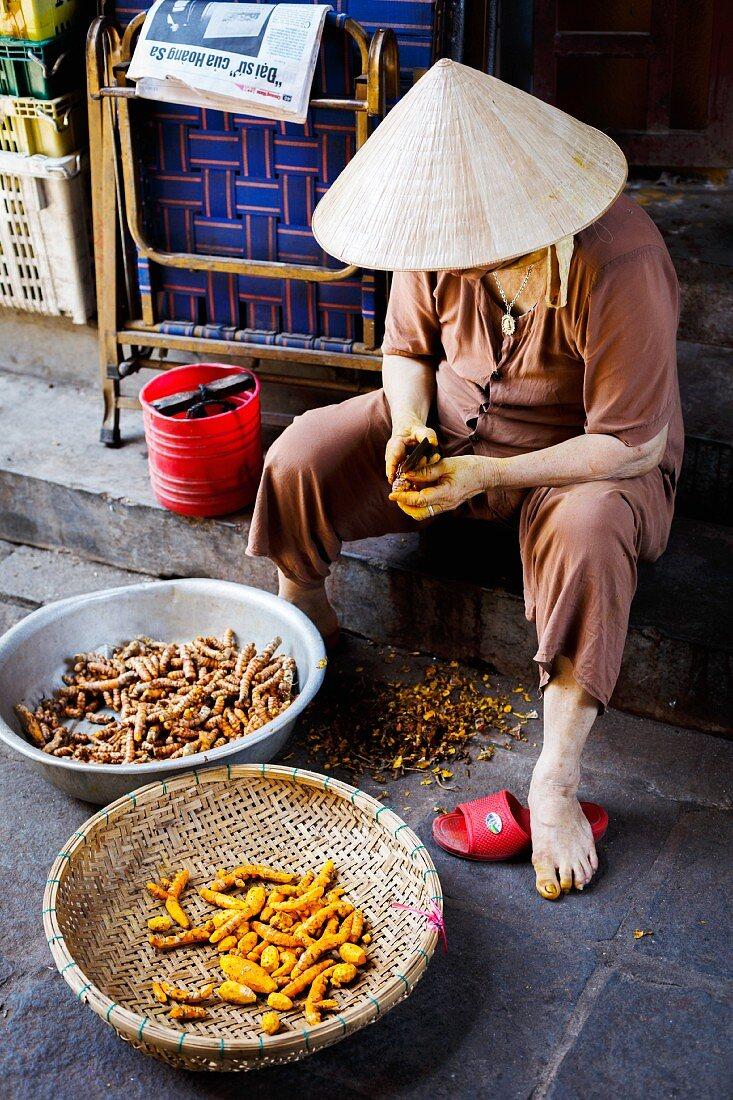 A woman peeling fresh turmeric in Hoi An, Vietnam