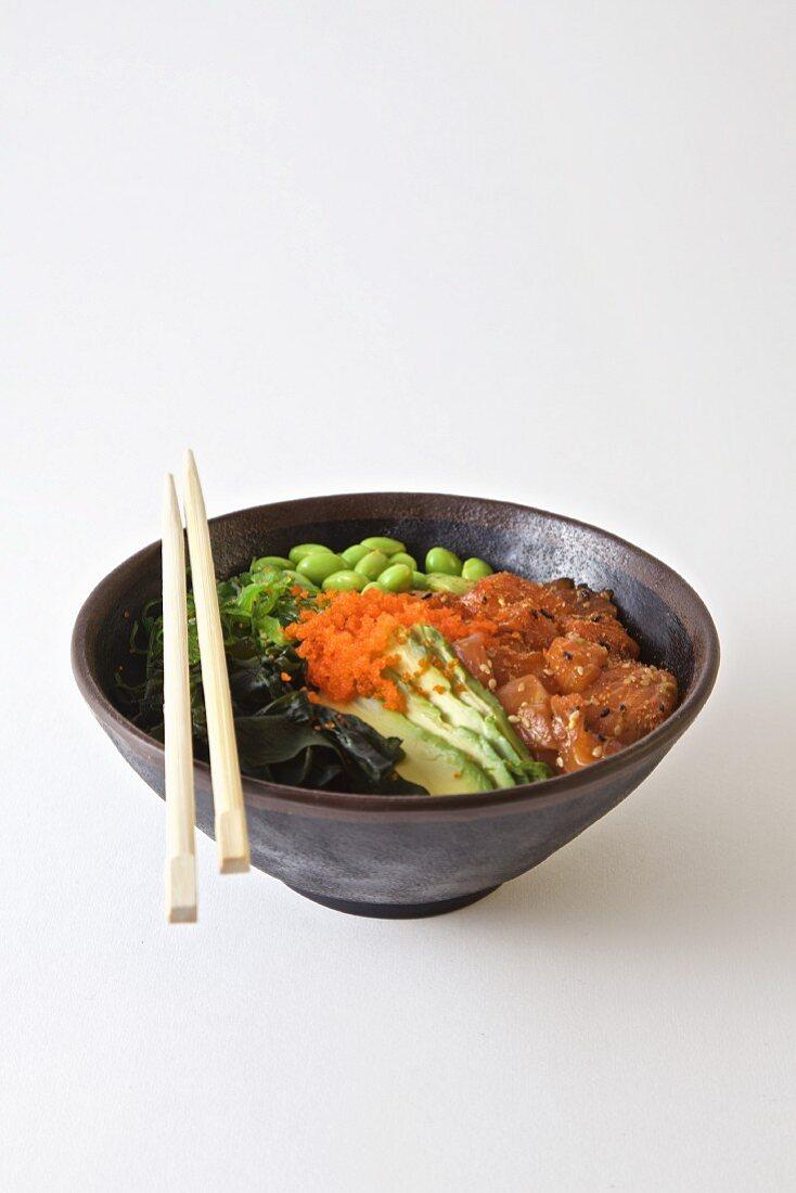 Poke bowl with salmon, edamame, seaweed and sesame oil