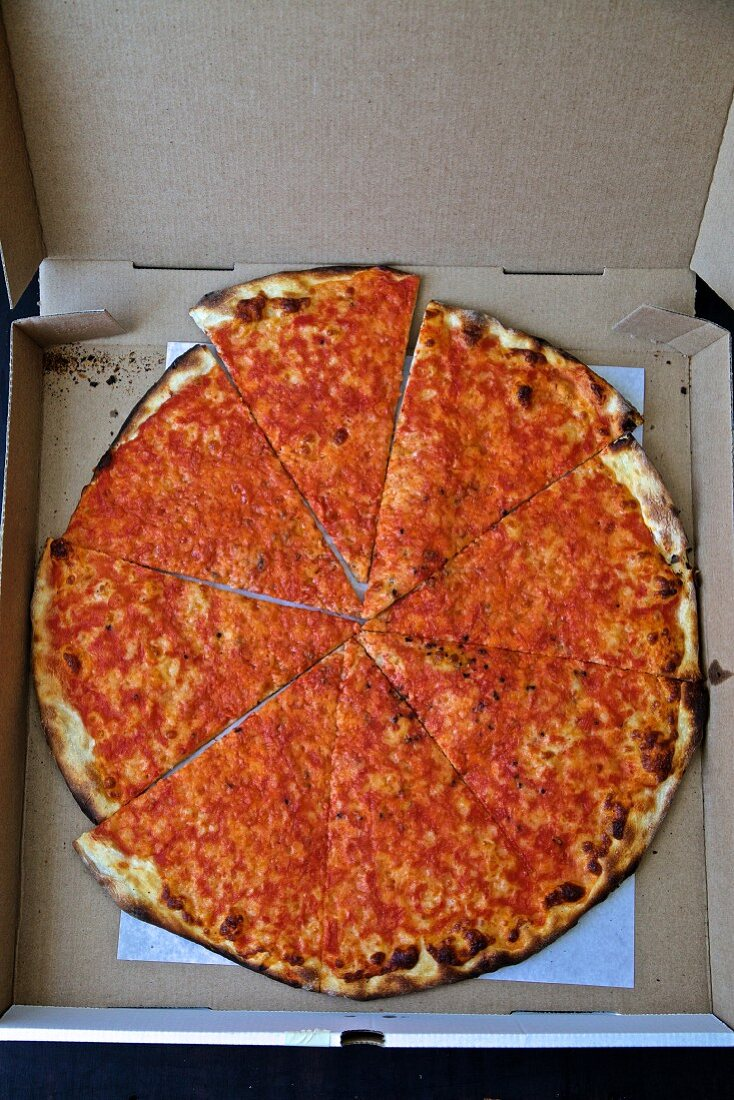 A pizza in an open delivery box (seen from above)