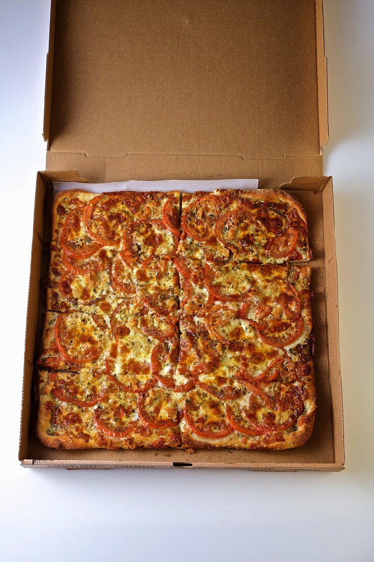 Tomato pizza in an open delivery box