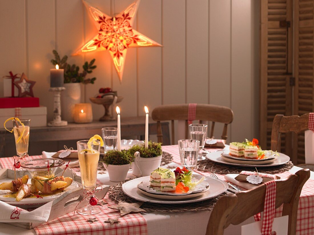 A festive Christmas table laid with servings of cucumber and salmon tureen and quince slices wrapped in bacon