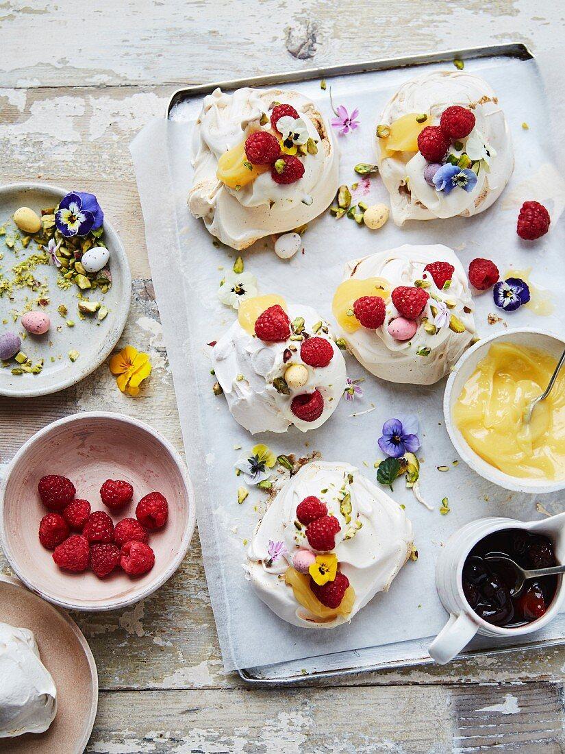 Lemon, raspberry, pistachio meringue with lemon curd, poached raspberries, and vanilla cream, edible flowers
