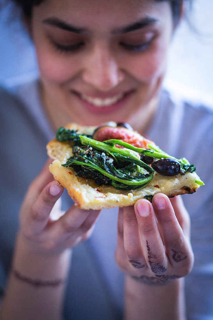 A slice of grilled pizza with rapini, figs, olives and blue cheese