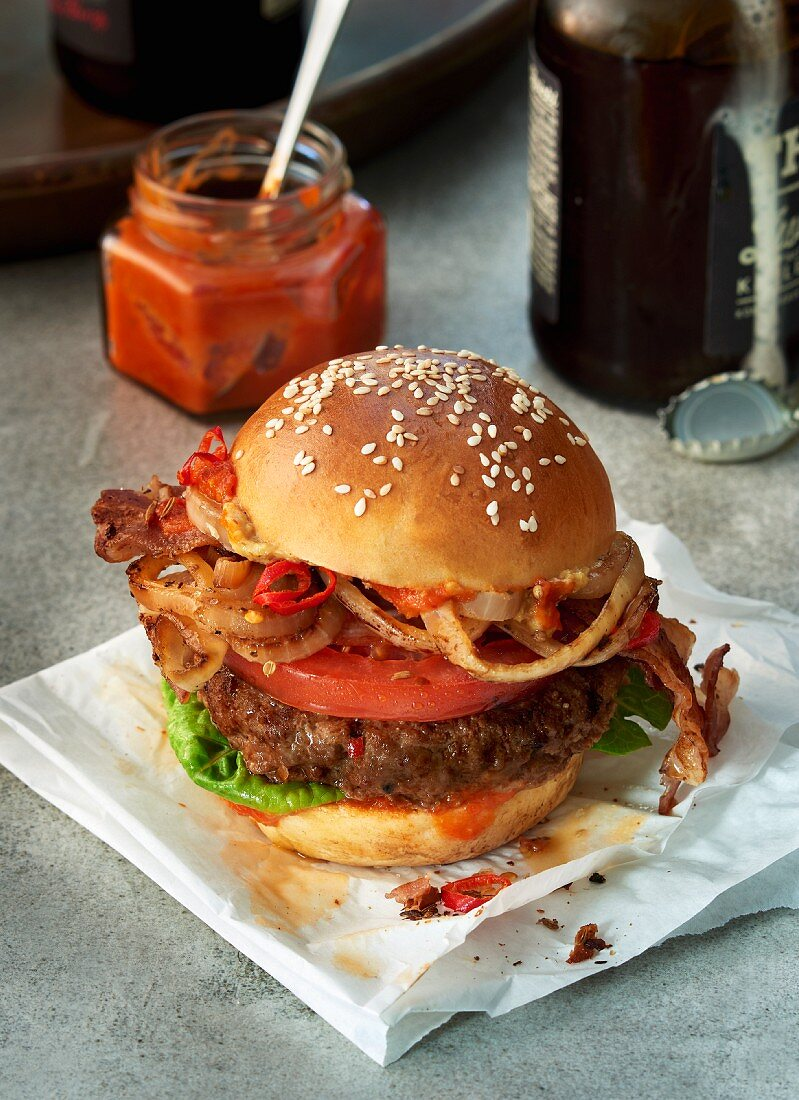 A hamburger with tomato, chili, bacon and onions