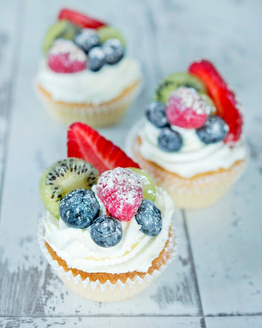 Cupcakes decorated with buttercream and fresh summer fruits