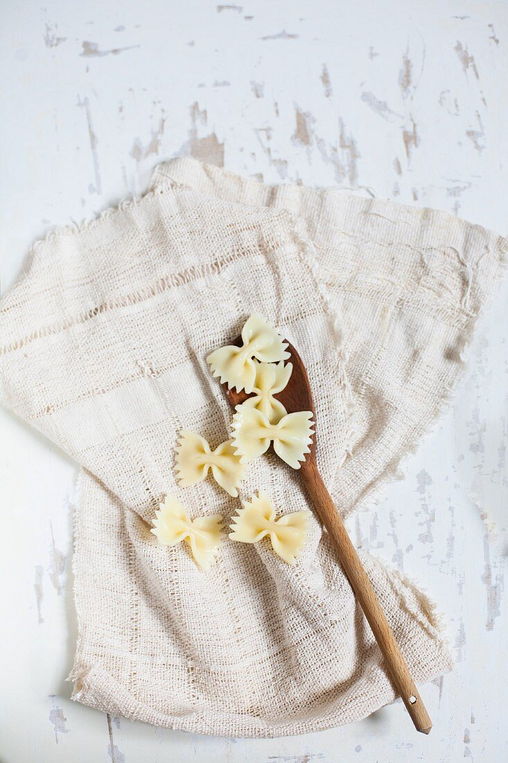Boiled farfalle with a wooden spoon on a cloth