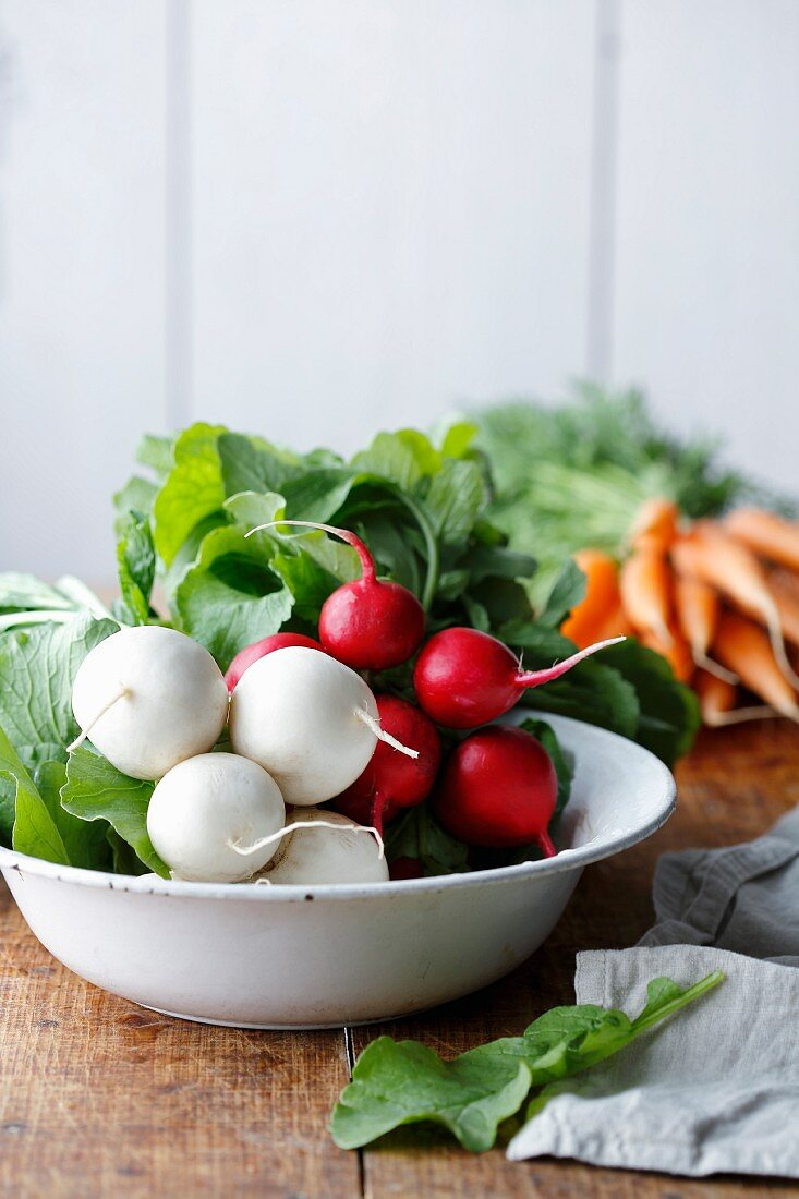 Radishes and carrots in a bowl, with carrots in the background