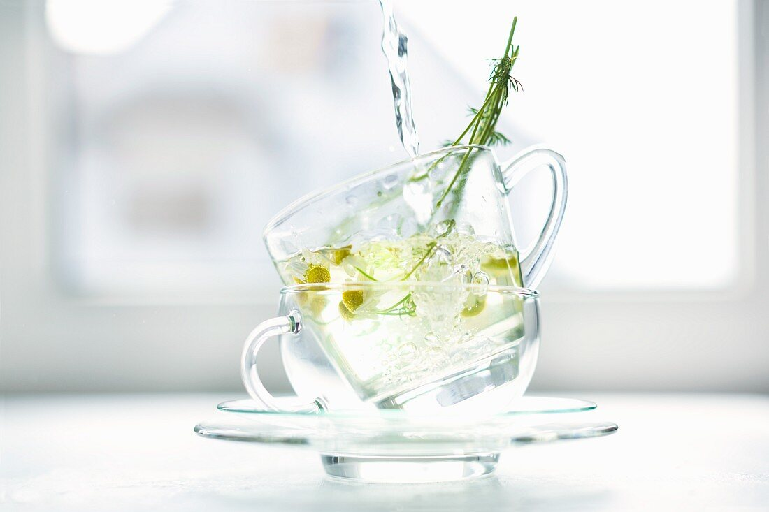 Hot water being poured over fresh chamomile blossoms in two glass cups stacked on top of each other