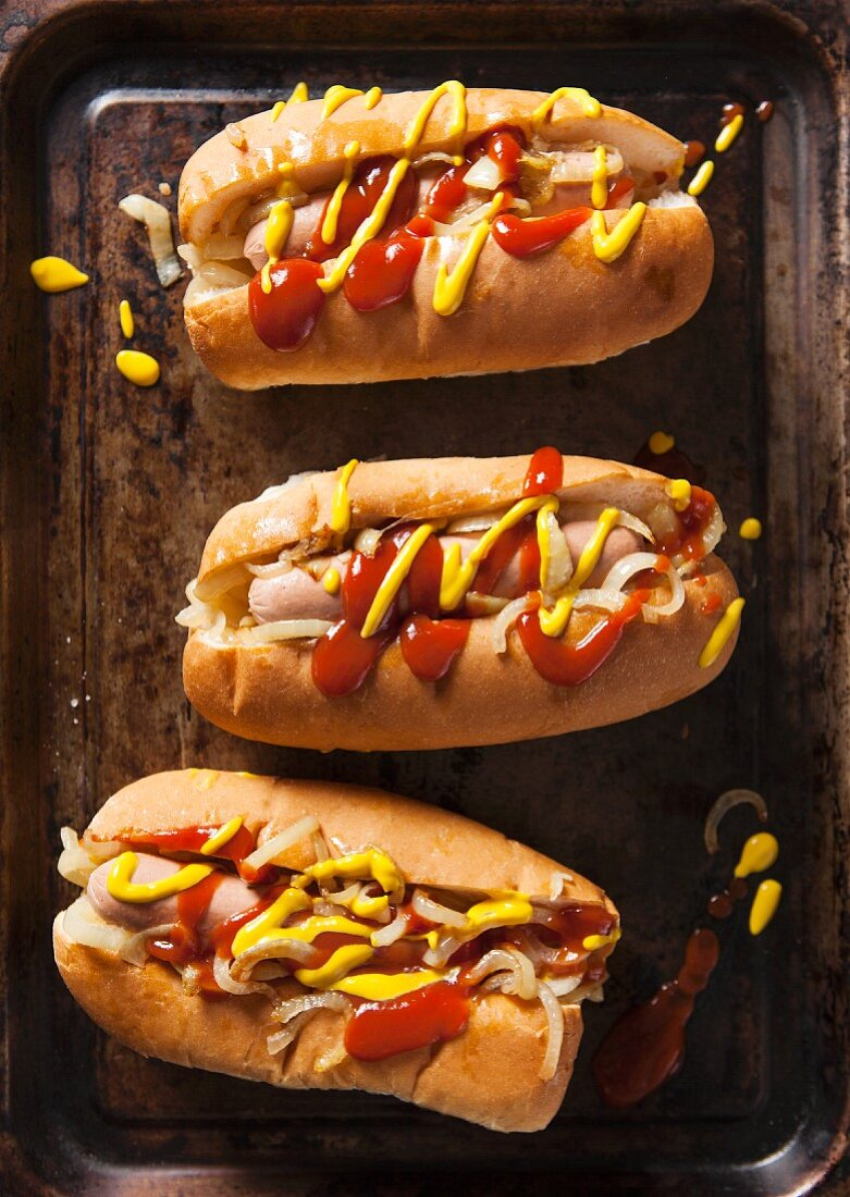 Three hot dogs in buns with ketchup, mustard and onions on a vintage baking tray