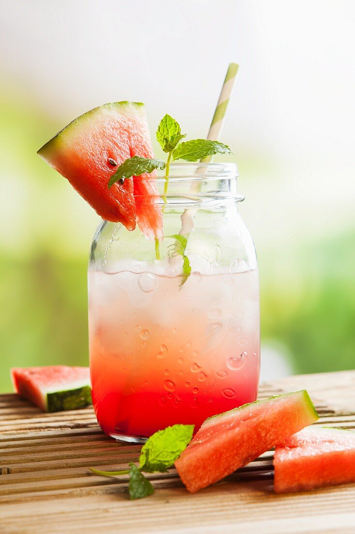 Fresh watermelon juice in a glass jar with ice on an outside picnic table