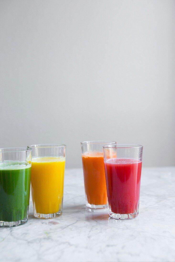 Various fresh cold-pressed juices (green juice, apple and lemon juice, carrot juice, watermelon juice)