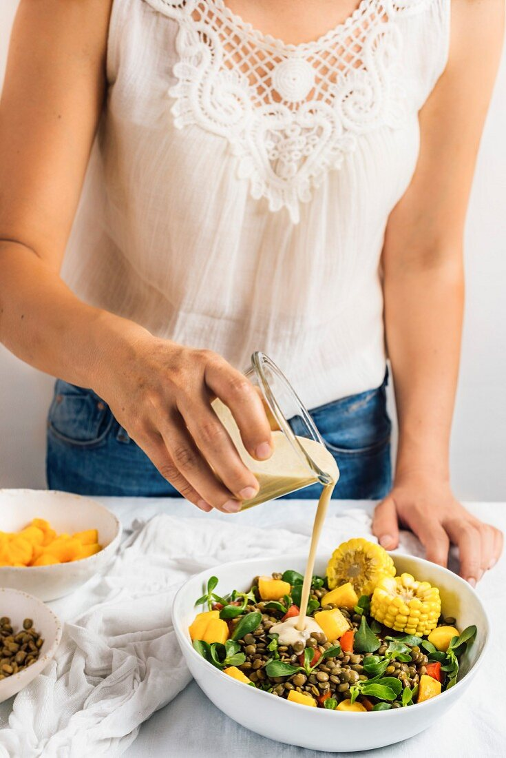 A woman wearing a white summer top and jeans pouring tahini dressing over lentil salad with sweetcorn and peaches