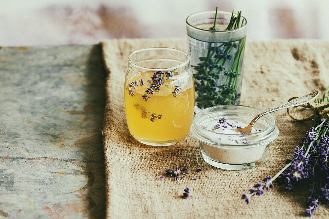 Organic raw honey, white sugar in glass jars, glass of water flavored with lavender flowers, standing on table with sackcloth