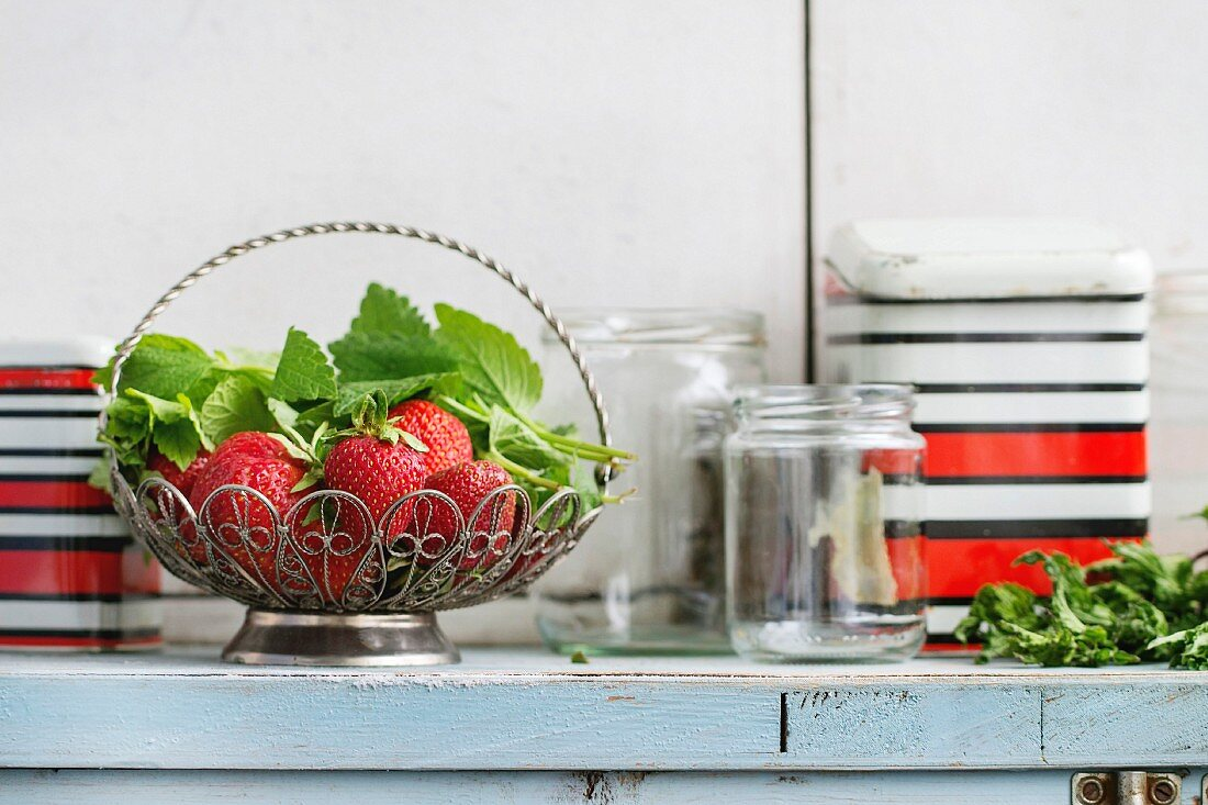 Fresh ripe garden strawberries and melissa herbs in vintage vase standing with empty glass and metal jars