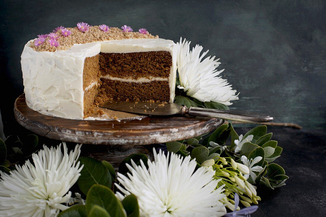 A marzipan almond cake with orange blossom mascarpone frosting and a slice cut out