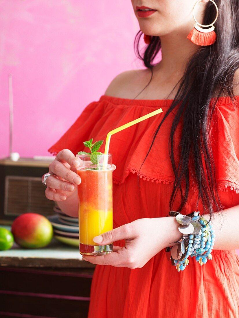 A woman drinking a mango strawberry daiquiri