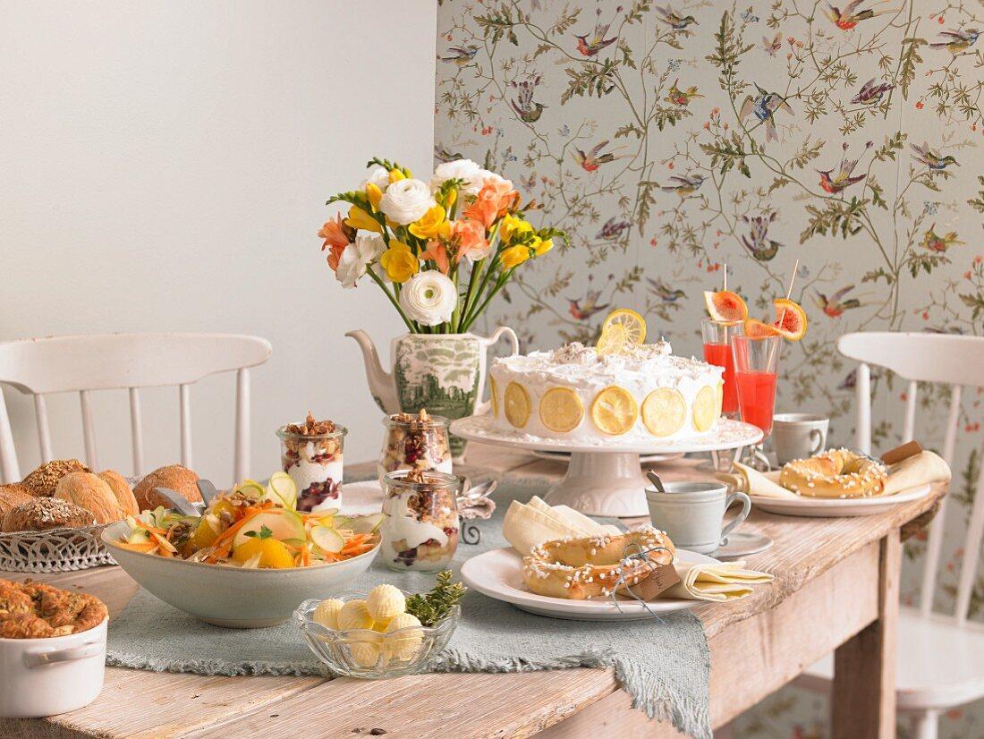 A breakfast table laid with lemon cake, pretzel hearts, granola, salad and souffle