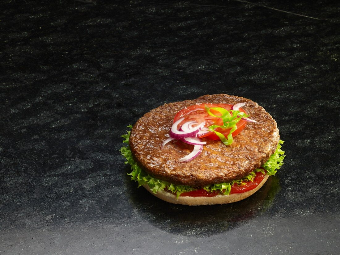 A hamburger on a halved burger bun