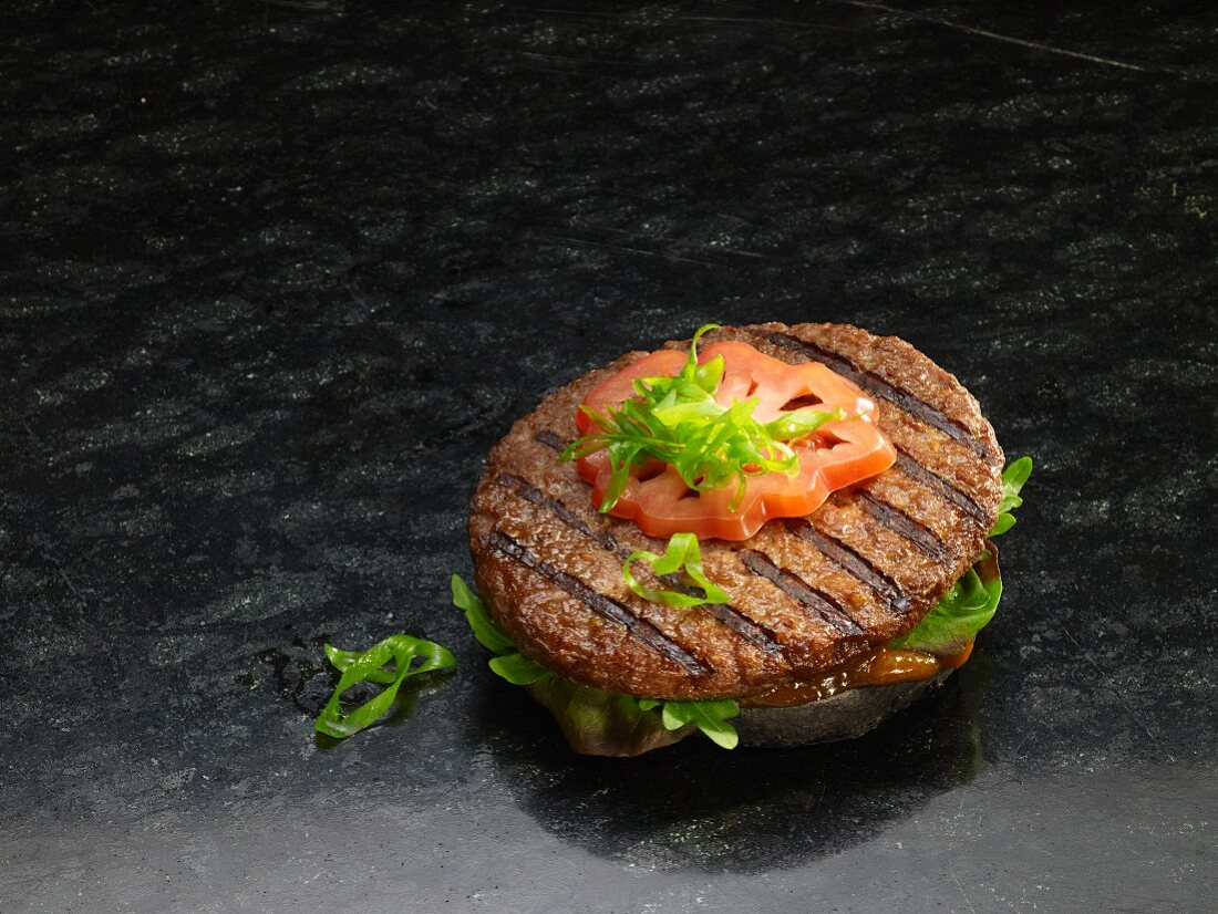 A grilled hamburger on a black bread roll