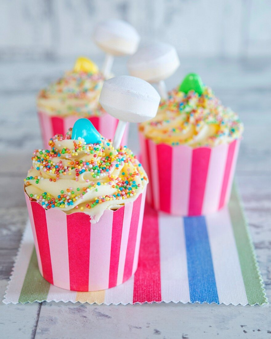Cupcakes with colourful sugar sprinkles and a lollipop