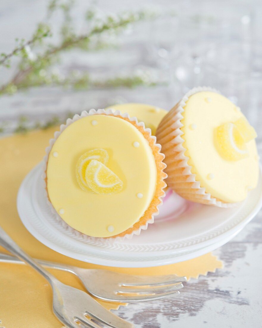 Lemon cupcakes with fondant icing and jelly sweets