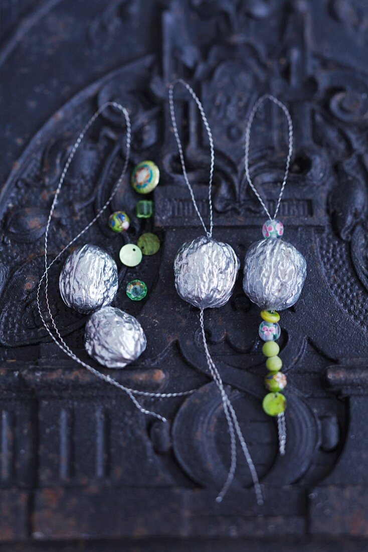Silver walnuts with decorative beads as tree decorations