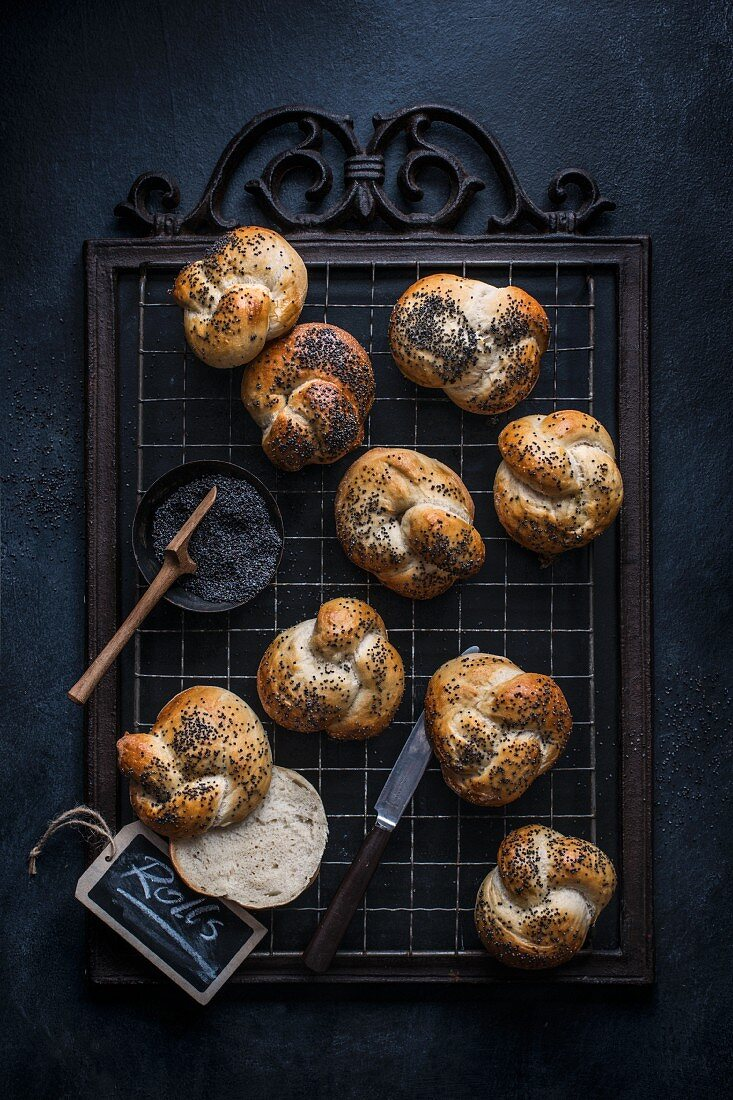 Freshly baked bread rolls with poppy seeds on a cooling rack