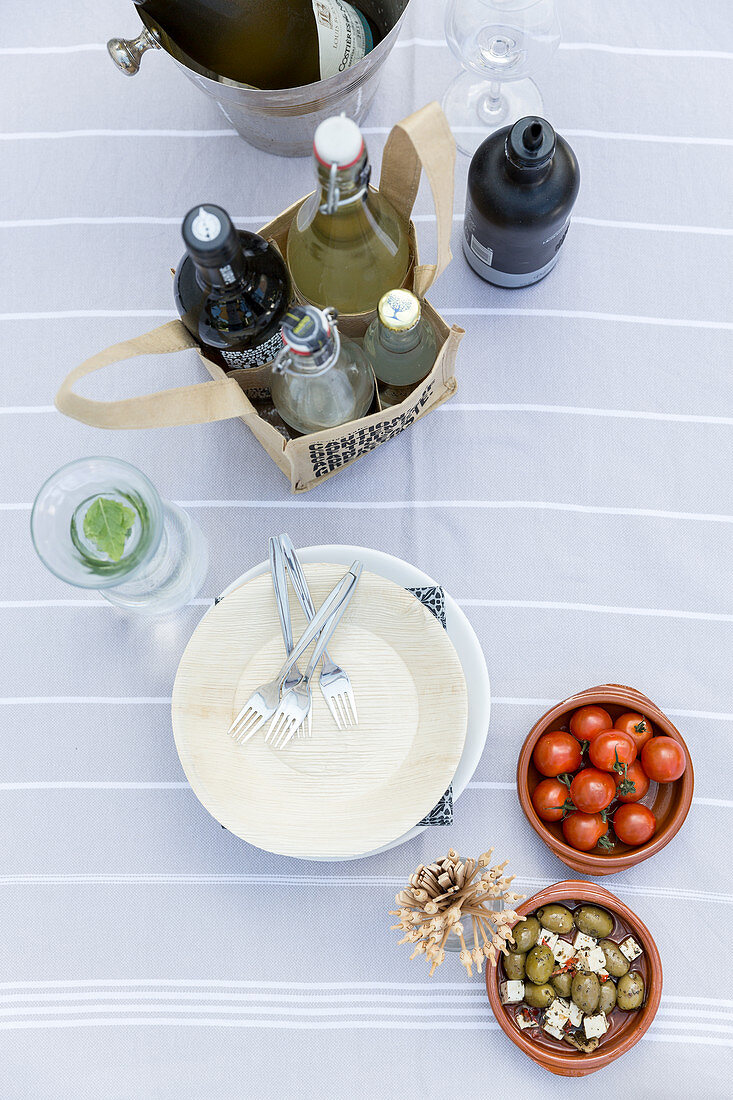 Ingredients for starters and drinks on terrace table seen from above