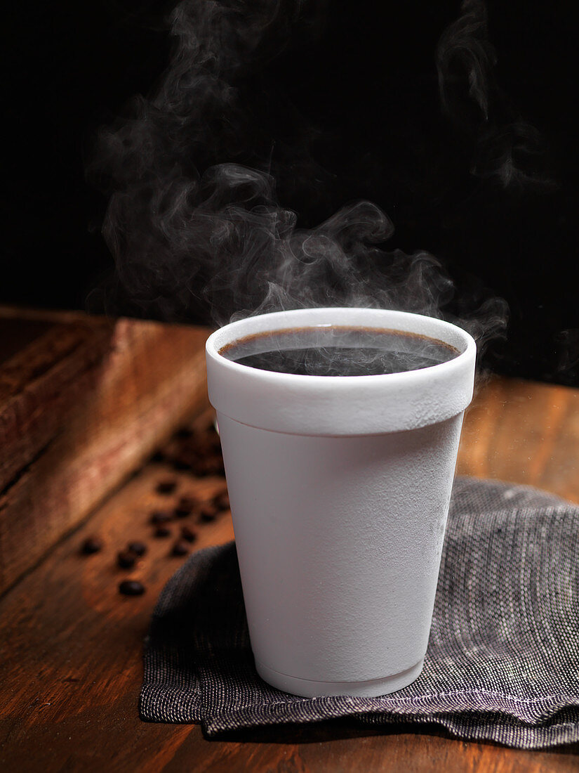 A cup of steaming hot black coffee in a polystyrene cup