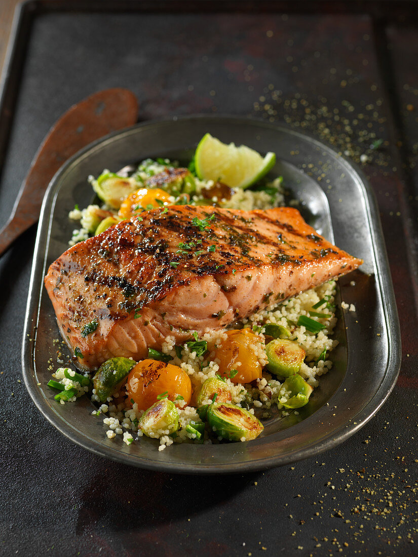 Grilled salmon fillet on a bed of couscous with vegetables