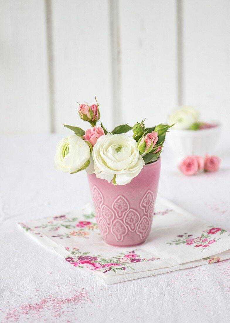 Ranunculus and roses in pink vase