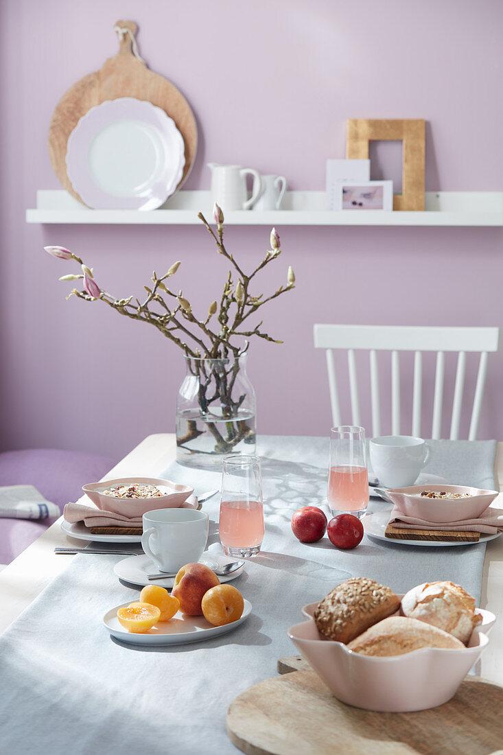 Vase of flowering magnolia on set breakfast table