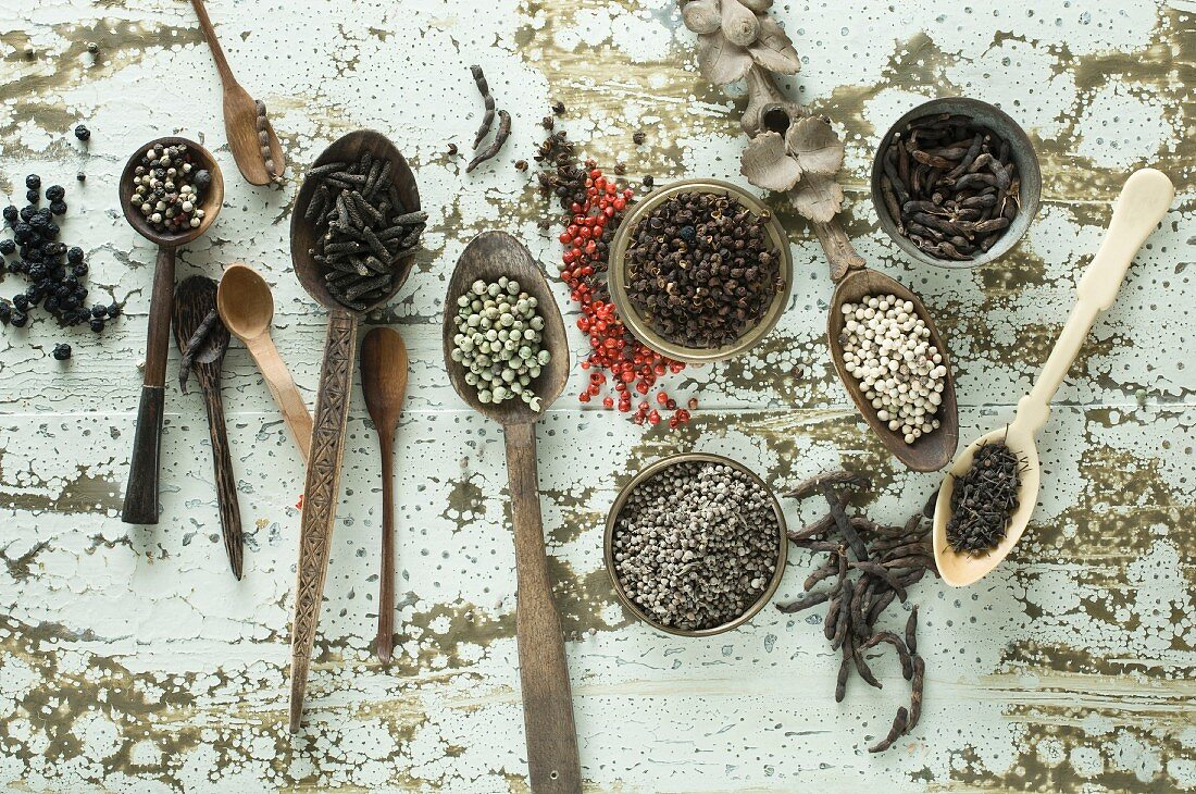Various types of pepper on spoons and in small bowls on a wooden background