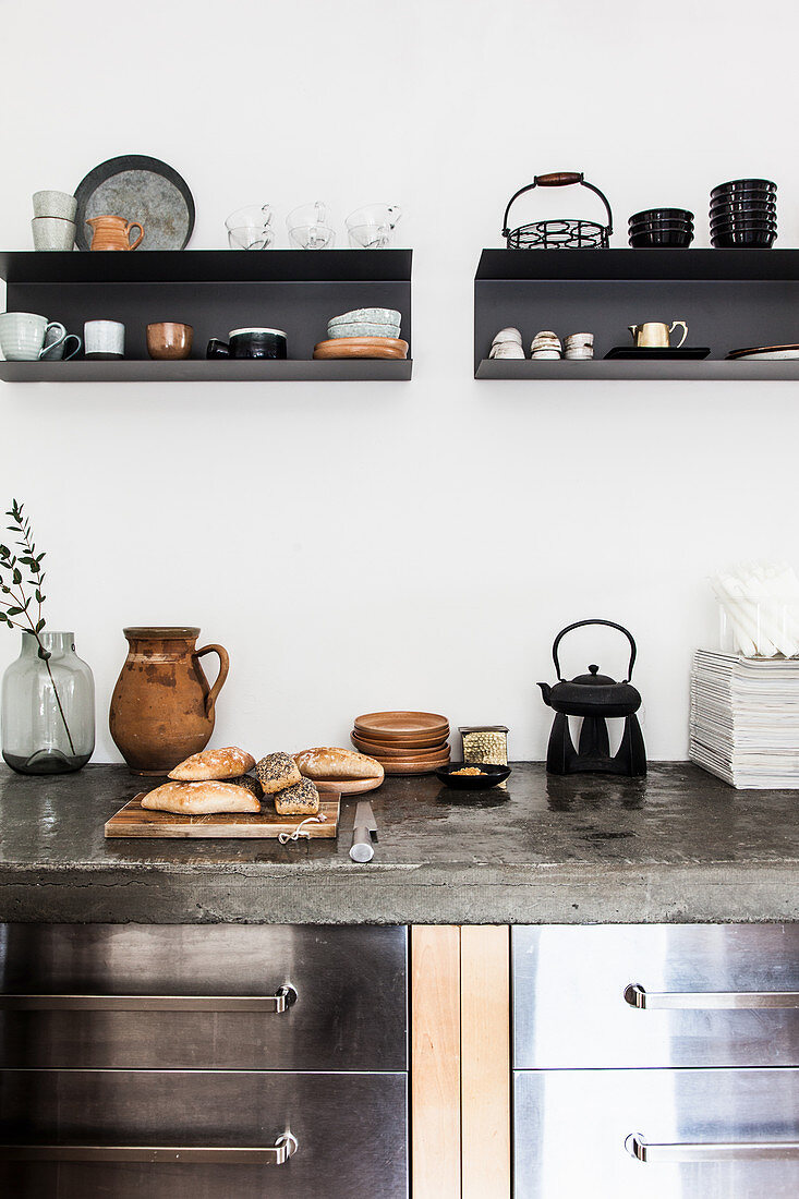 Bread rolls on wooden chopping board on concrete worksurface in kitchen