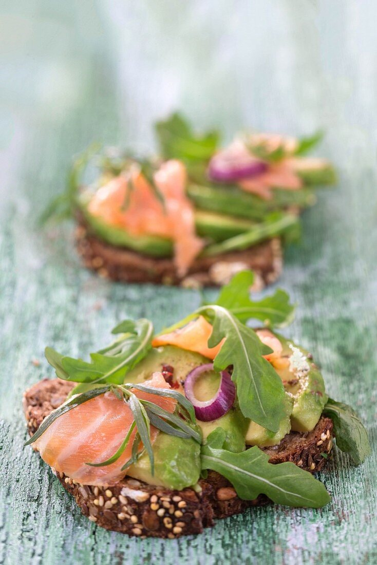 Wholegrain bread topped with avocado slices, salmon and rocket