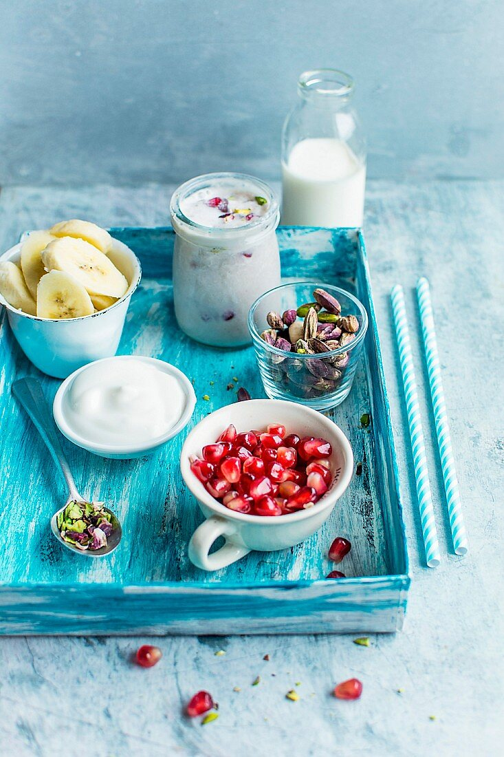 Yoghurt with pomegranate seeds, banana, pistachios and milk