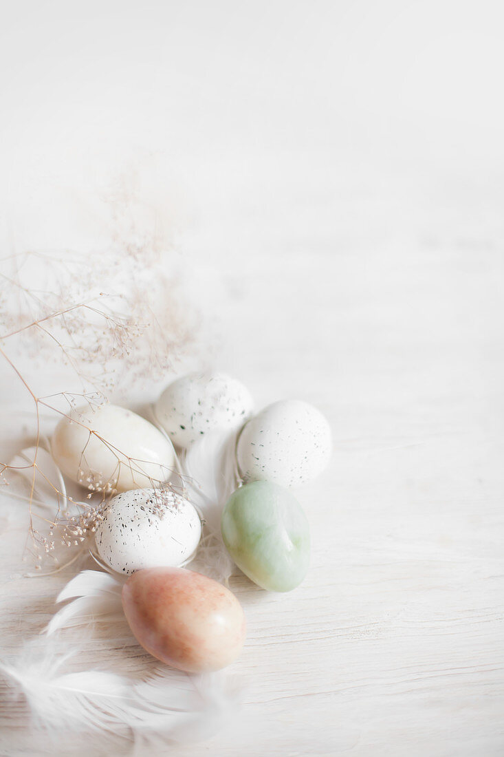 Easter eggs and feathers on white wooden surface