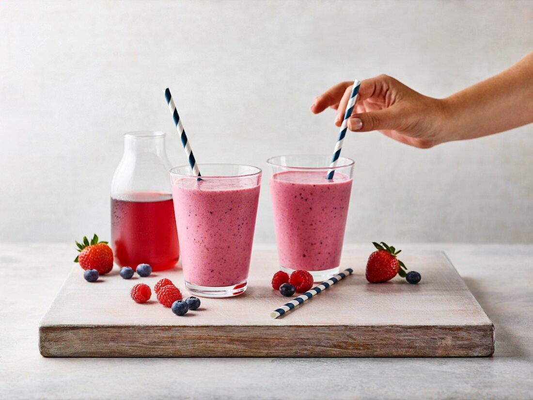 A hand holding a straw in a berry smoothie