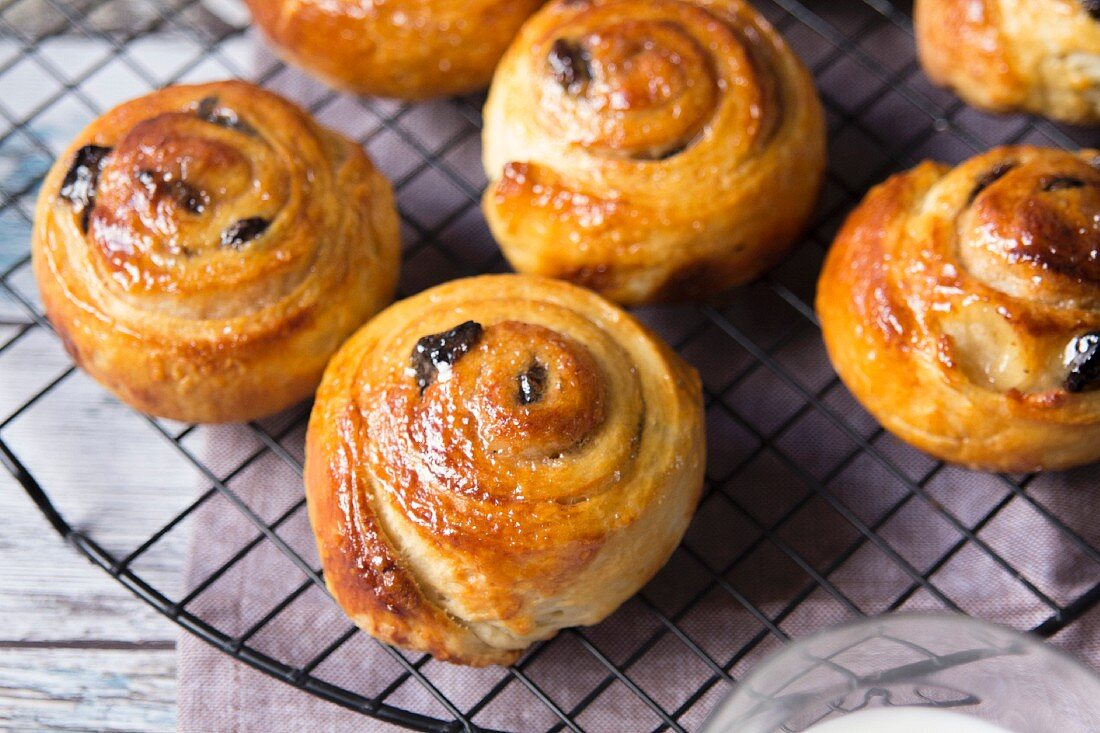 Cinnamon swirls with raisins on a wire cooling rack