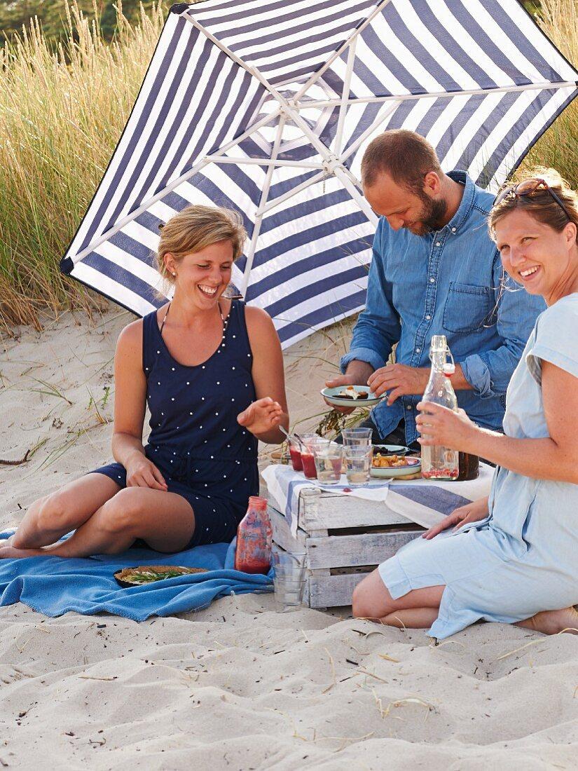 Three people having a picnic at the beach