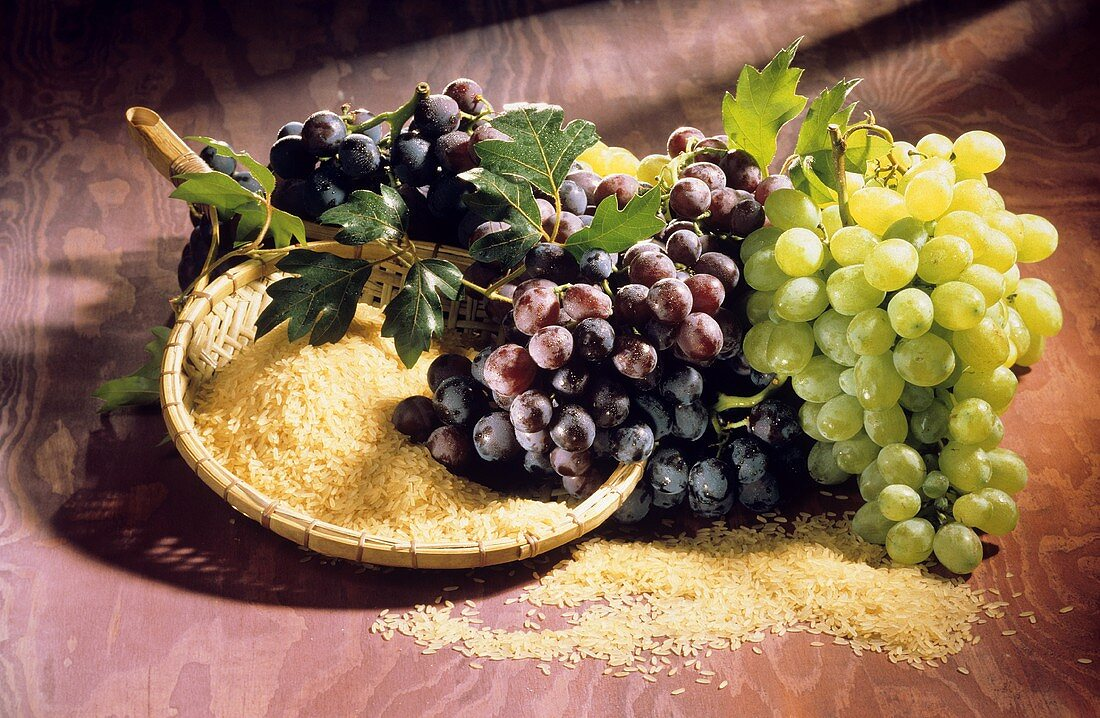 Still life with white & red wine grapes & a bowl of rice