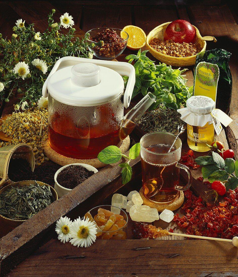 Still life with teapot, tea glass & many types of tea & sugar