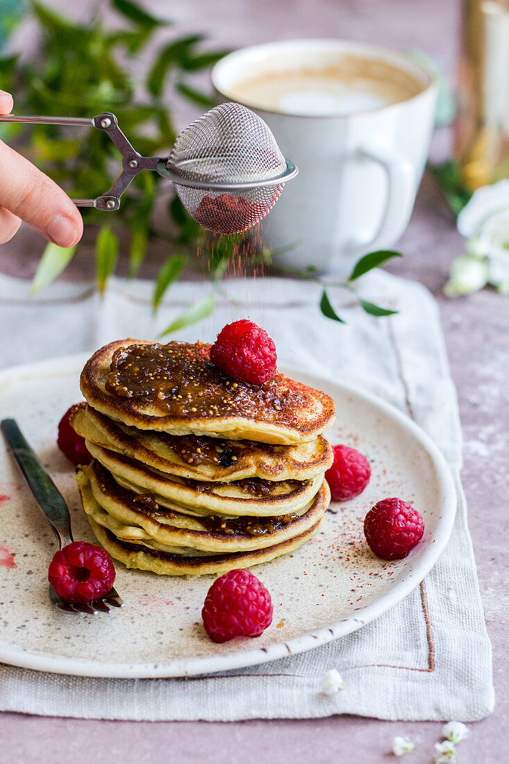 Pancakes with raspberies with fig jam, sprinkled with strawberry powder, served with coffee