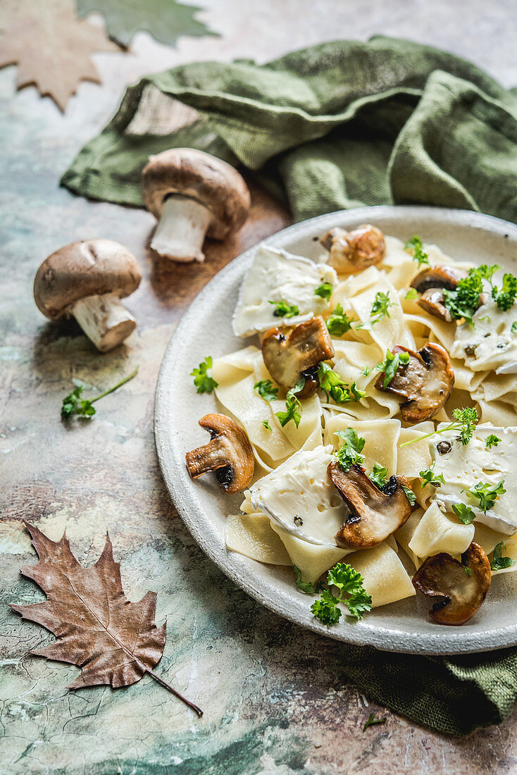 Autumn pasta with mushrooms, camembert with pepper and parsley
