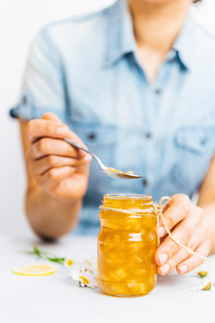 Woman with a blue shirt taking a spoon of lemon jam from a jar