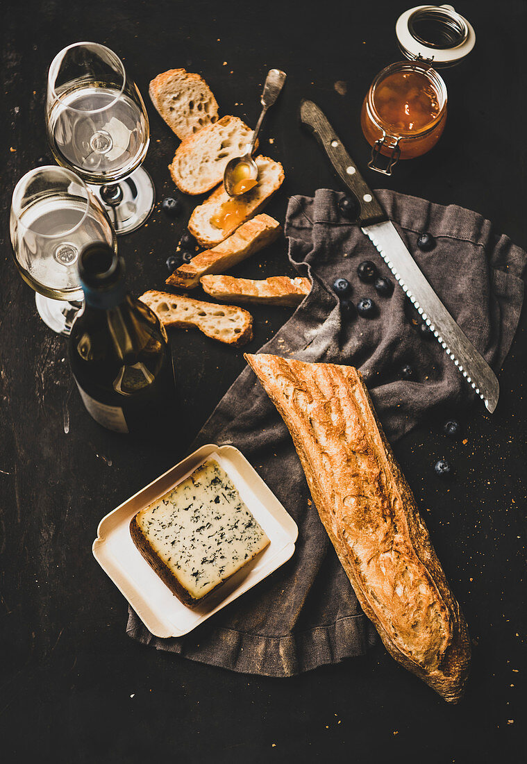 Sliced baguette, cheese, apricot jam, berries and white wine over rustic black background