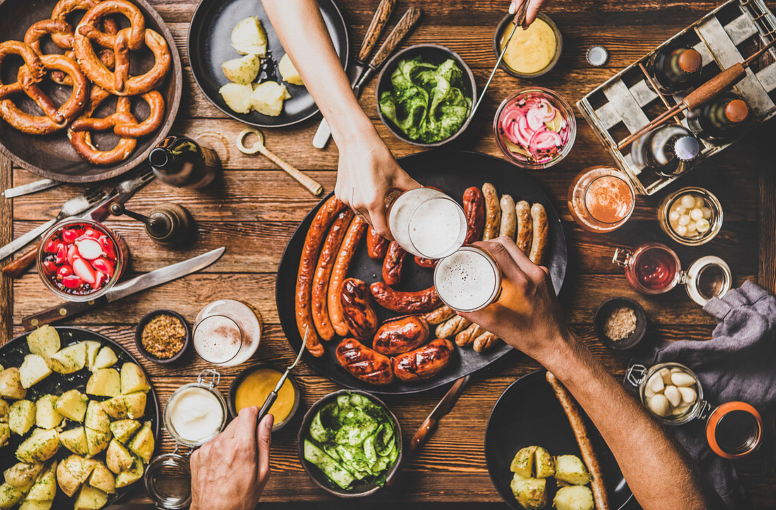Octoberfest dinner table with grilled meat sausages, pretzel pastry, potatoes, cucumber salad, sauces, beers and peoples hands clinking glasses