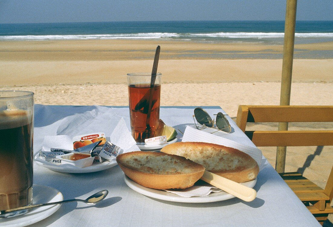 Table with rolls, jam, tea, coffee at seaside in Andalusia